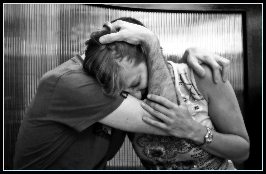 two people upset and embracing each other