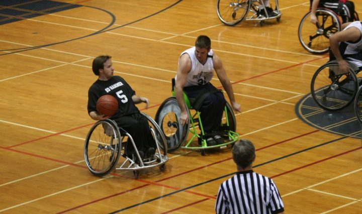 two men in wheelchairs playing basketball