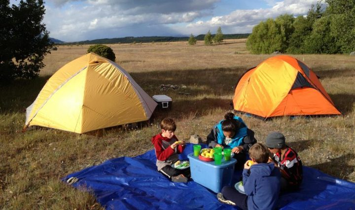 two tents and a family enjoying a camping holiday
