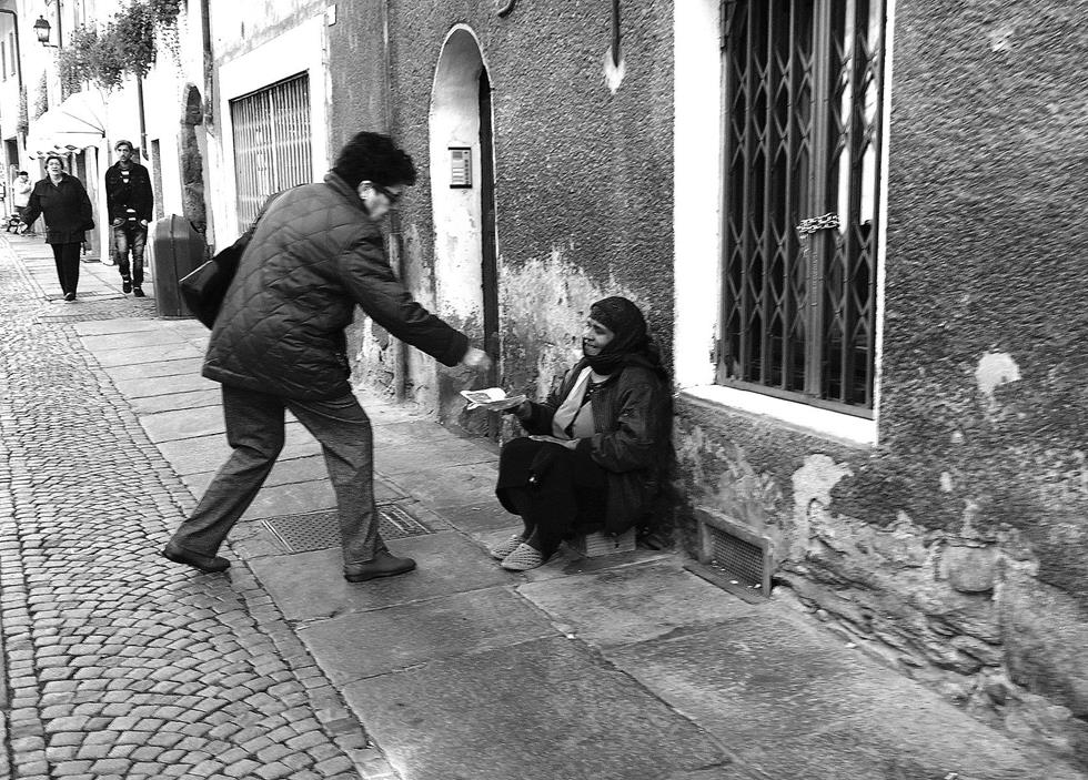 man gives money to beggar on street